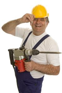 Arbeiter mit Bohrhammer und Schutzhelm